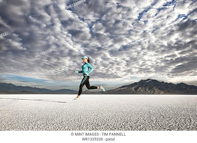 A young woman running through the landscape on the salt flats surface near Salt Lake city