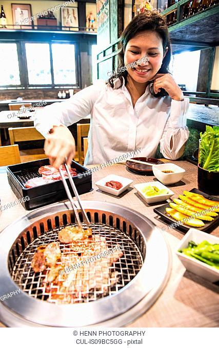 Woman at Japanese style bbq restaurant, Bangkok, Thailand