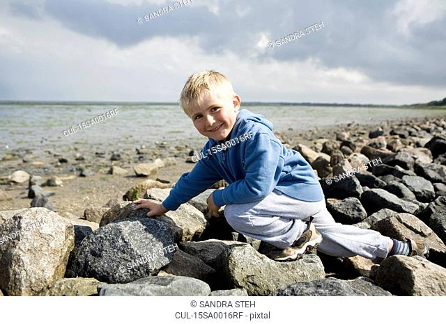 Boy walking over stones