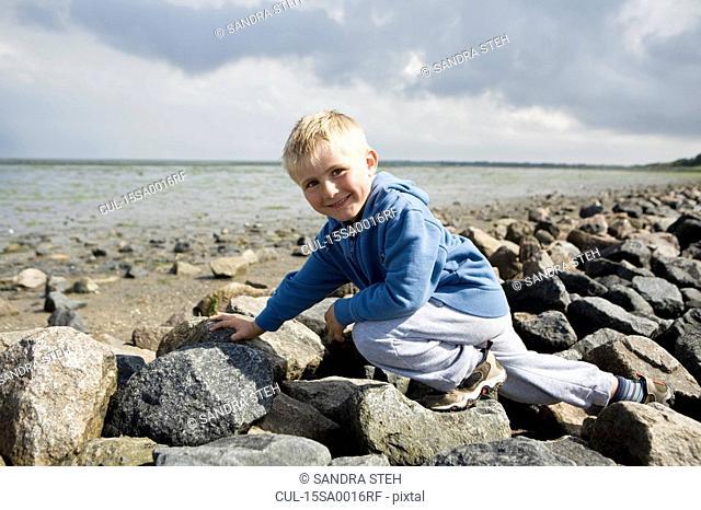 Boy walking over stones