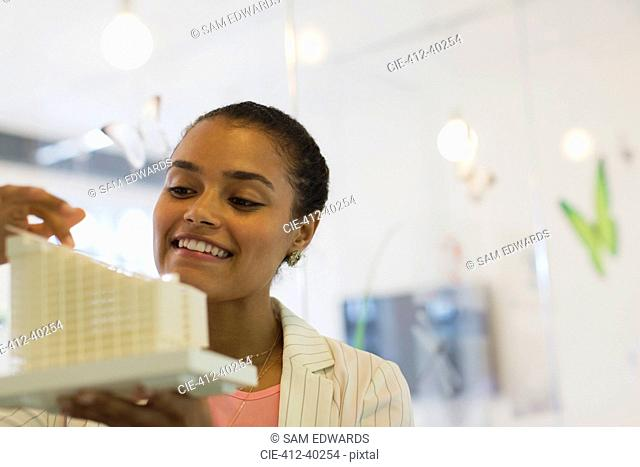 Smiling, confident female architect examining model in office
