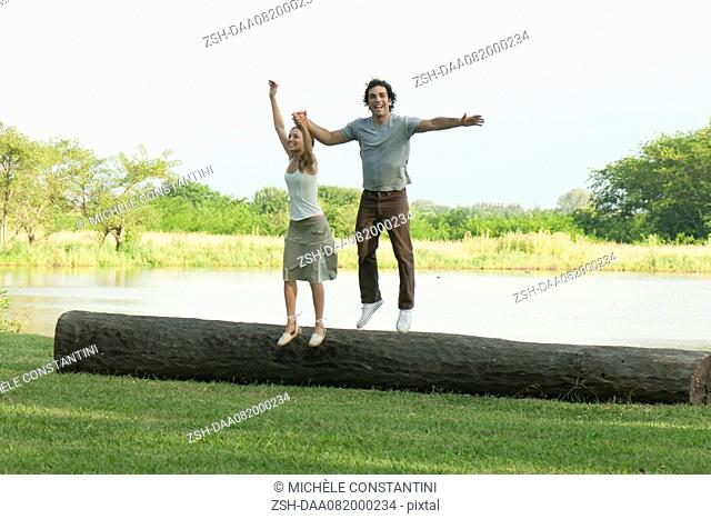Young couple jumping off log in park
