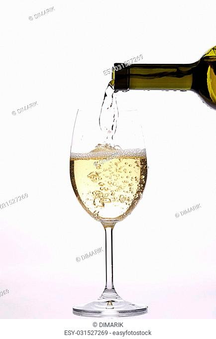 poruing white wine with drops and sparkle from bottle