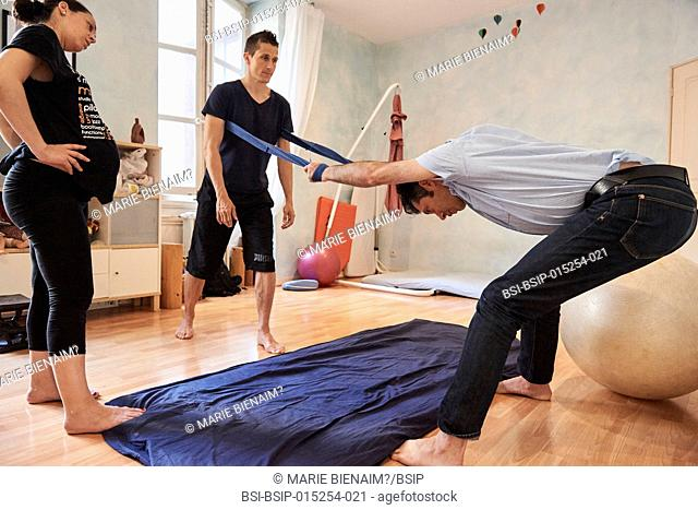 Reportage on a midwife in Lyon, France during antenatal classes for couples. Discovering and working on positions that will help ease the physiological birth