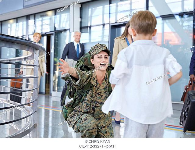 Son running greeting soldier mother at airport