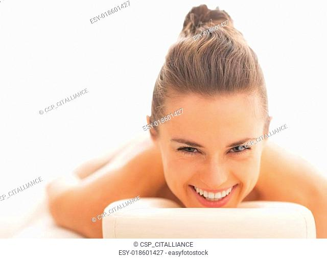 Smiling young woman laying on massage table