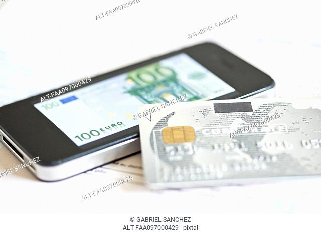 Credit card resting on smartphone displaying one-hundred euro banknote