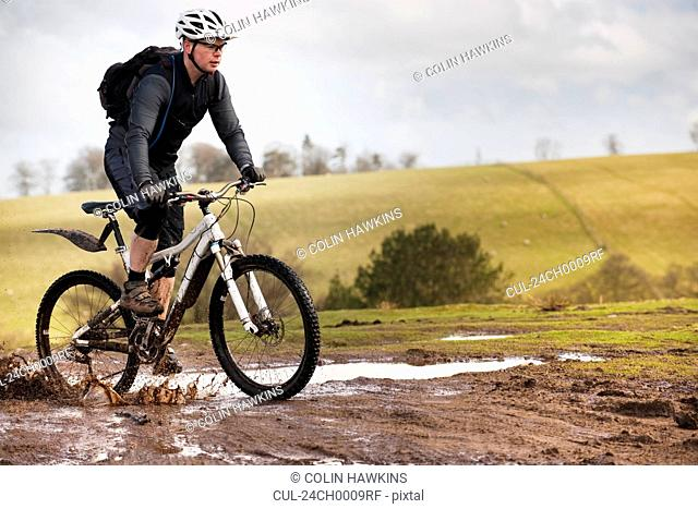 Man riding mountain bike through mud