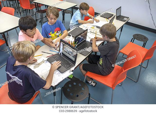 Caucasian and Asian American boys work at laptops in a Boys and Girls Club computer lab in Laguna Beach, CA