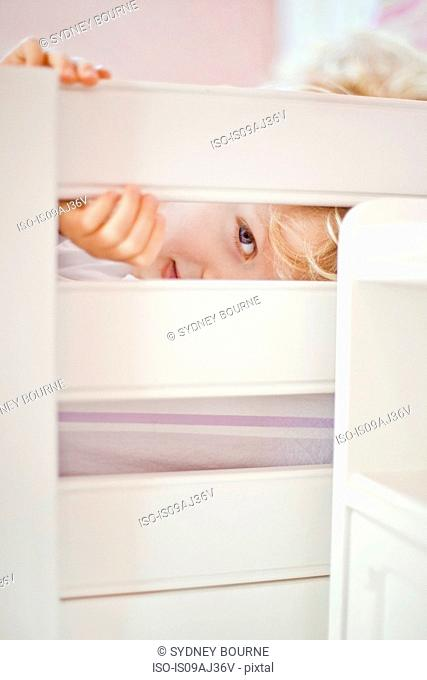 Close up portrait of four year old boy peeking through bed frame