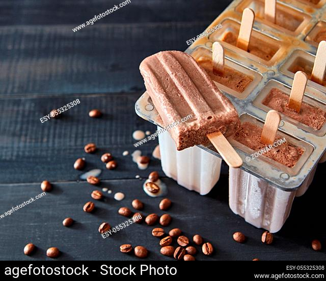Cooking chocolate ice creame and candies in ice pop molds on a wooden background with copy space. Homemade prepare concept