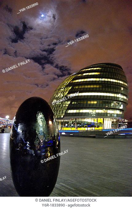 London City Hall at night under a full moon with egg-shaped sculpture in the foreground