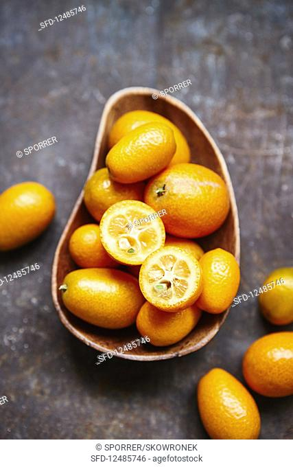Kumquats, whole and halved, in a wooden bowl