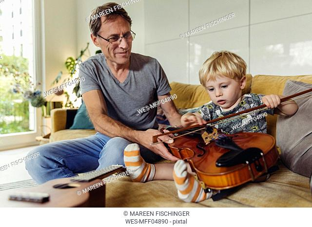Portrait of toddler testingviolin while his father watching