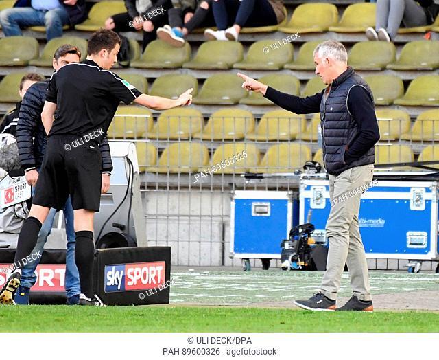 Karlsruhe coach Mirko Slomka (R) speaks with referee Lasse Koslowski during German 2nd division Bundesliga soccer match between Karlsruher SC and FC Wuerzburger...