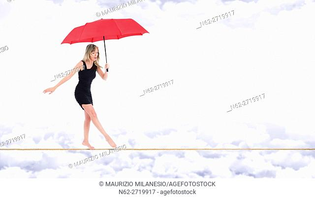 Barefoot woman, walking very focused on a rope with a red umbrella in hand, on the bottom white clouds in a blue sky