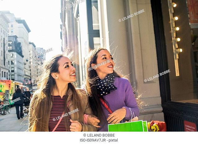 Young female adult twins with shopping bags looking up at shop window