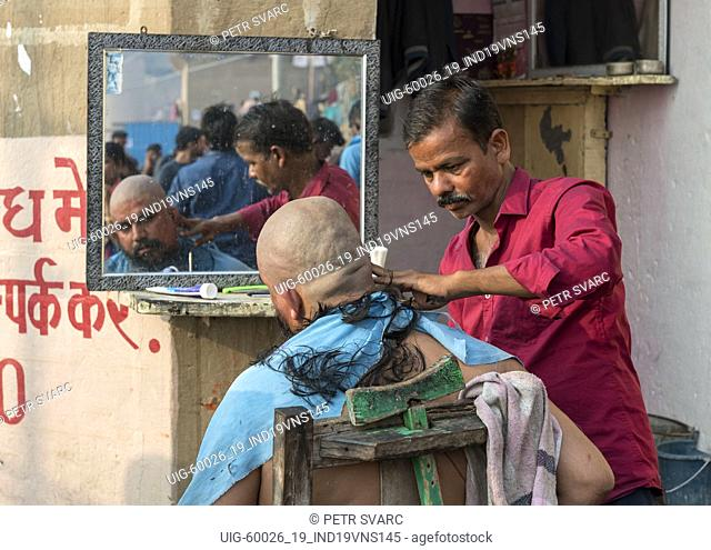 Street barber shop on the ghats of the River Ganges, Varanasi, India
