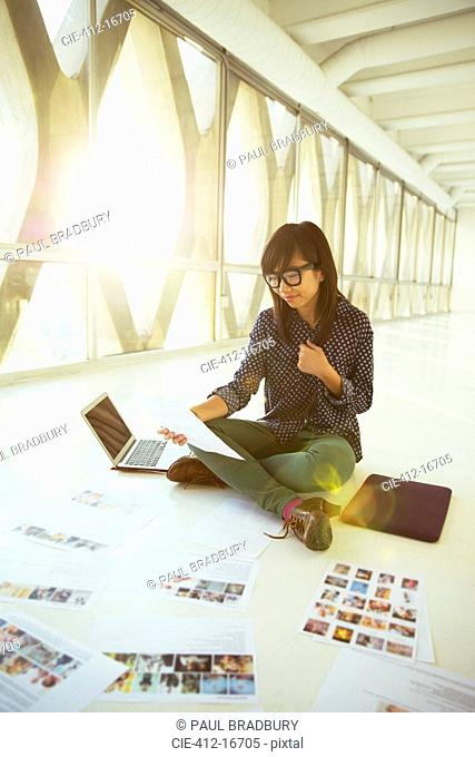 Creative businesswoman looking at photograph proofs on office floor