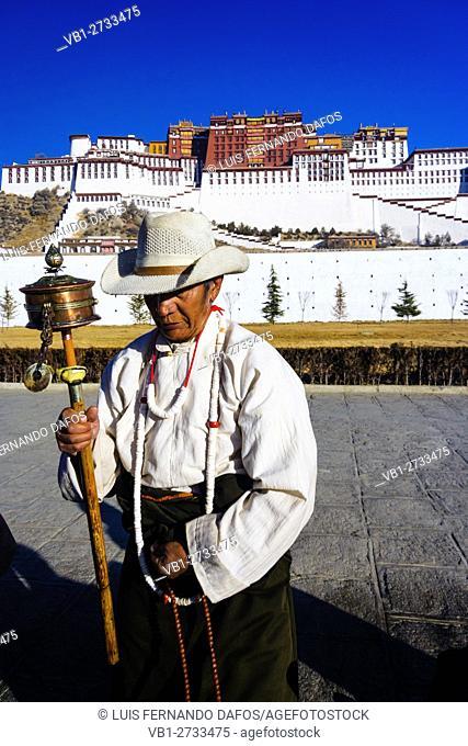 Pilgrim with prayer wheel by Potala Palace . Lhasa , Tibet