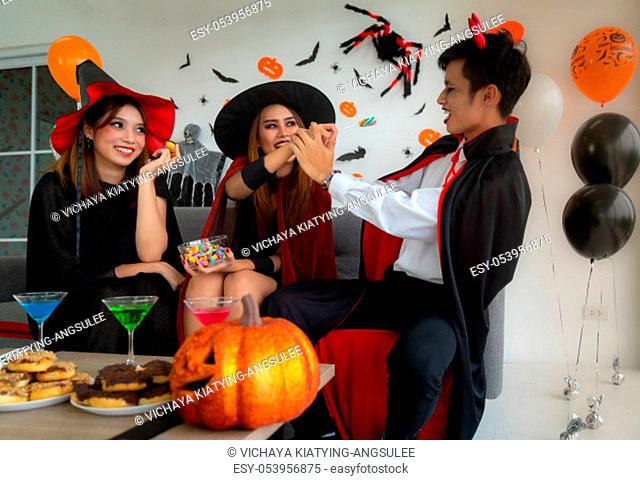 Group of young adult and teenager people celebrating a Halloween party carnival Festival in Halloween costumes with food and drink on table