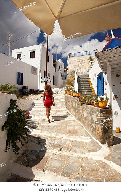 Woman walking in the alley of the Faros village, Sifnos, Cyclades Islands, Greek Islands, Greece, Europe