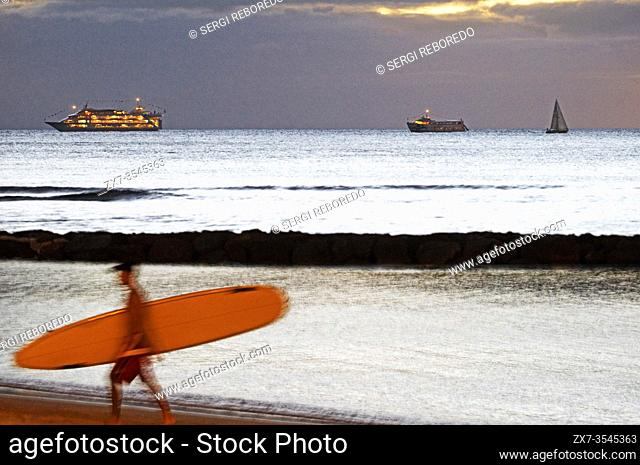 Surf and cruises, two of the most repeated words on the beaches of Waikiki Beach. O'ahu. Hawaii. Surfer on the famous Waikiki Beach