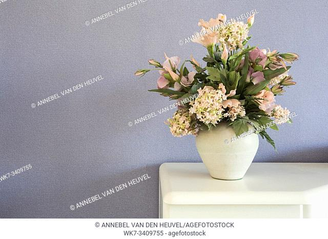 Fake flowers in white vase on the table with purple wall background texture vintage