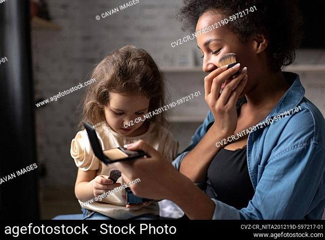 Ethnic woman showing daughter how to apply makeup