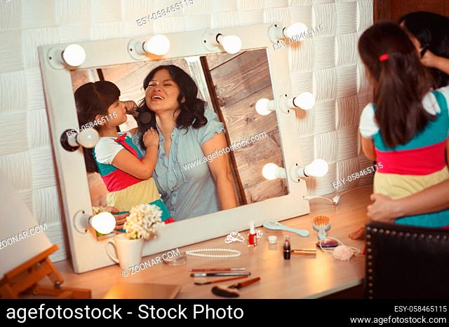 Little daughter doing makeup to her mother in front of huge mirror. Picture of mather and daughter having fun, good time at home or in studio