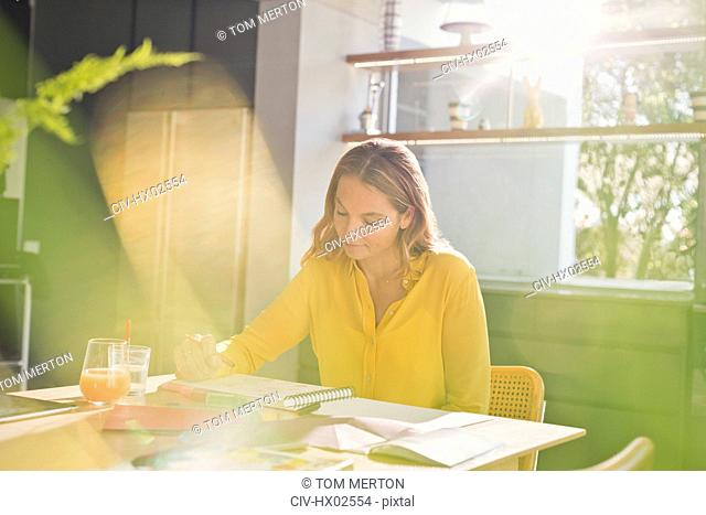 Woman drawing at sunny kitchen table