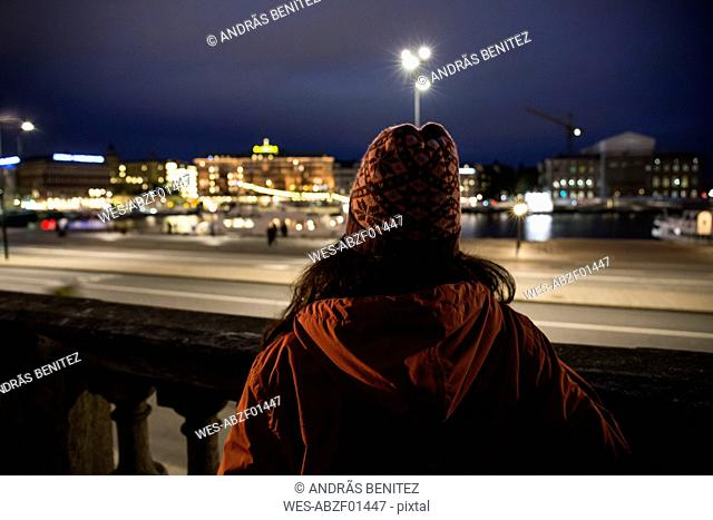 Back view of woman looking to the city by night