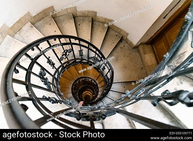 High angle view of spiral staircase with hand of man below