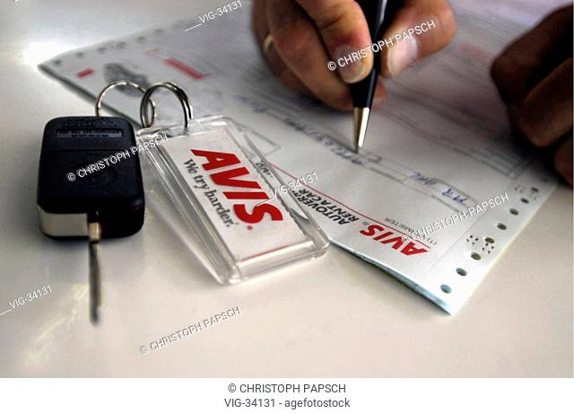 Symbolic picture: car rental. Filling out of a rental contract. On the table a car key with keychain - AVIS -. - BONN, GERMANY, 11/06/2003