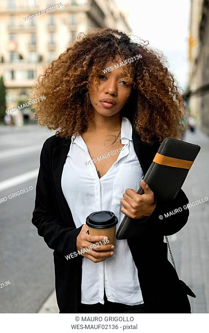 Young woman with laptop bag and coffee to go in the city, missing the taxi