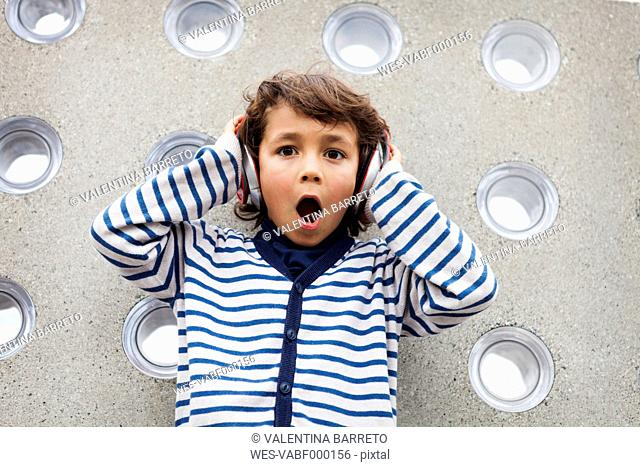Portrait of astonished little boy listening music with headphones