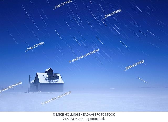 Moon lights a foggy winter scene over western Iowa as stars trail above a barn