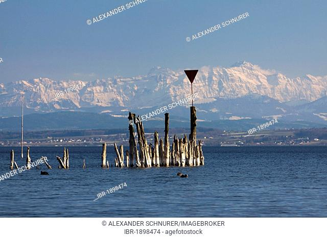 Remains of old jetty at Lake Constance with the peak of Mt Saentis, Alpstein massif, at back during foehn weather conditions, Baden-Wuerttemberg, Germany