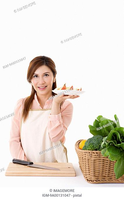 Housewife holding a plate of chopped apple
