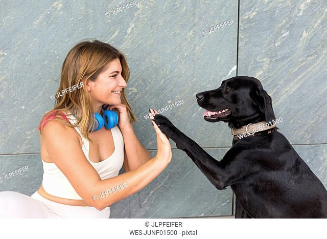 Happy young woman with her black dog