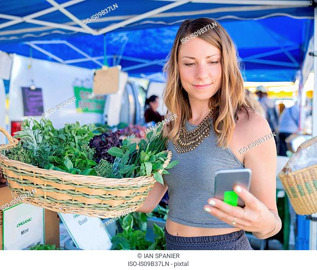 Woman at fruit and vegetable stall holding basket of fresh herbs looking at smartphone