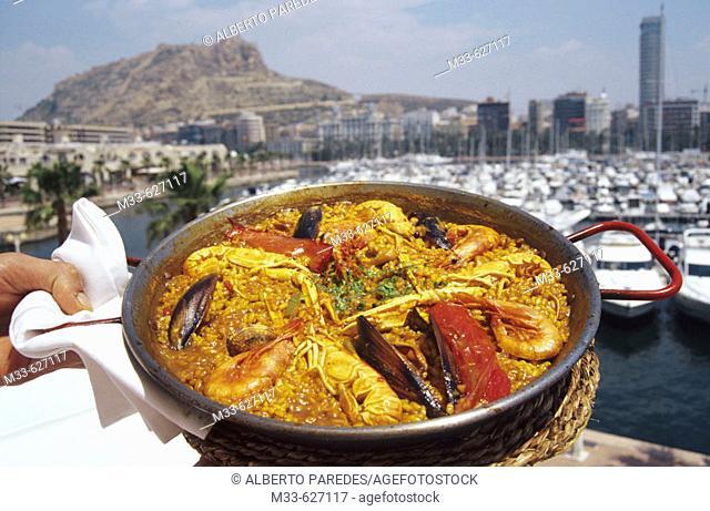 Seafood Paella in 'Los Titorros Restaurant' at the harbour. Santa Barbara Castle in background. Alicante. Comunidad Valenciana. Spain
