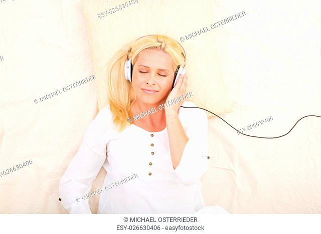 A middle aged woman listening to music with headphones in bed