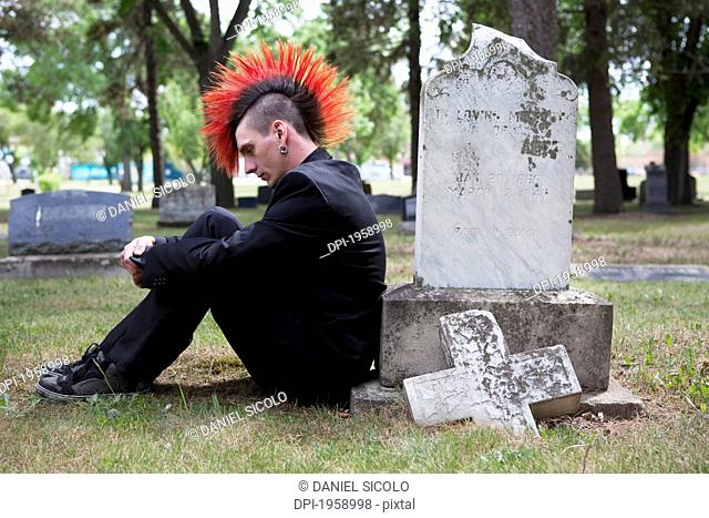 A Young Man With A Red Mohawk Sits Alone By A Tombstone In A Cemetery; Edmonton, Alberta, Canada