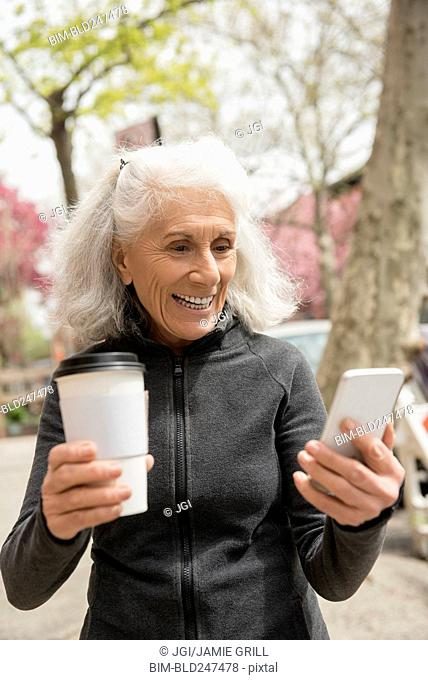 Older woman drinking coffee and texting on cell phone