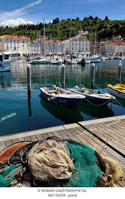 Fishing nets on dock of Piran Slovenia with boats and sailboats moored in harbor on the Adriatic Sea coast