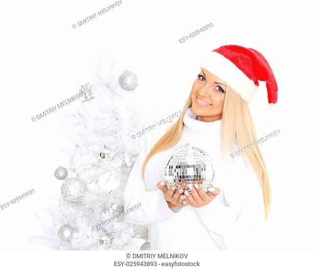 Young woman in Santa Claus cap with mirror ball stands near Christmas tree on a white background