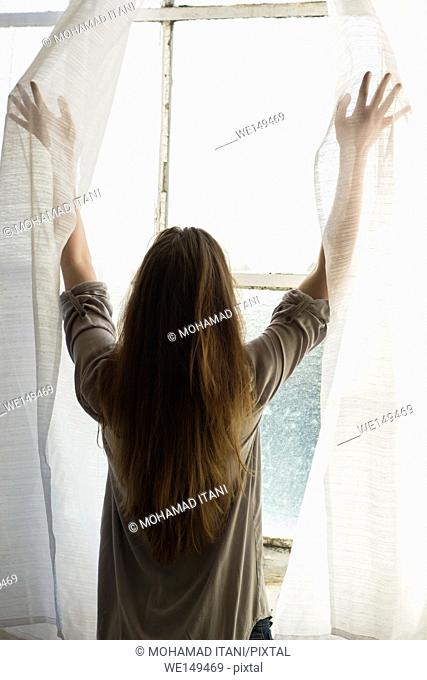 Rear view of a woman opening the blinds