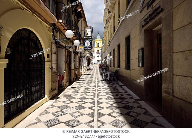 Pedro Romero street with cafe restaurants and Socorro parish church in Ronda Spain