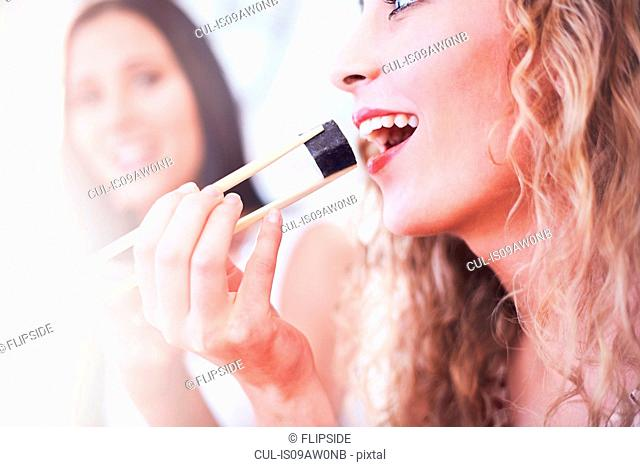 Close up of two female friends eating sushi with chopsticks in kitchen